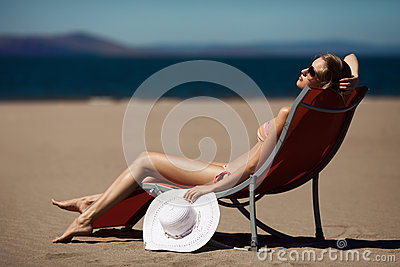 Beautiful woman on a deckchair at the beach