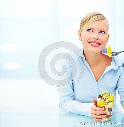 Beautiful woman at desk eating fruit salad