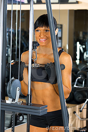 Beautiful woman is doing exercises at the gym