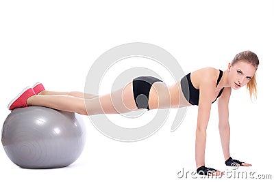 Beautiful woman doing push ups on fitness ball