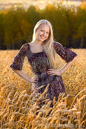 Beautiful woman in dress at the wheat field