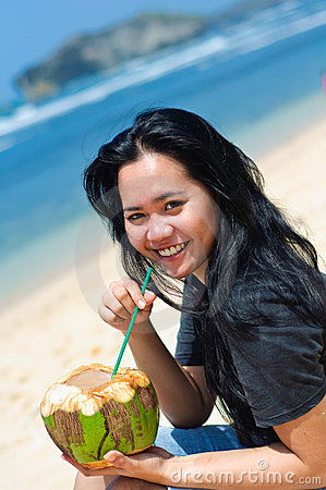 Beautiful woman drinking coconut water