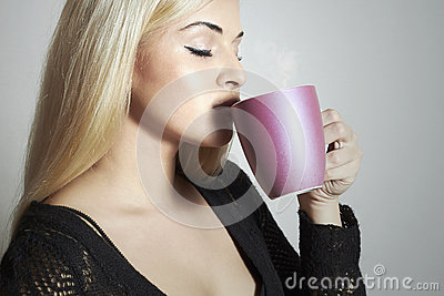 Beautiful woman drinking Coffee. Blond Girl with Cup of tea