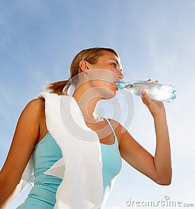 Beautiful woman drinking water during exercising