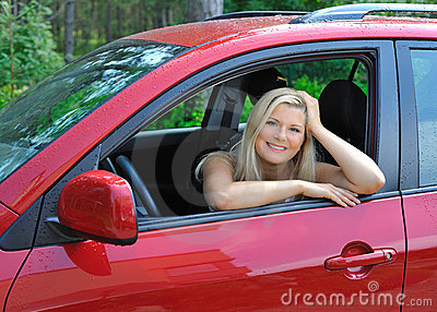 Beautiful woman driver in red shiny car outdoors
