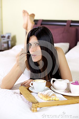 Beautiful woman eating with spoon in bed