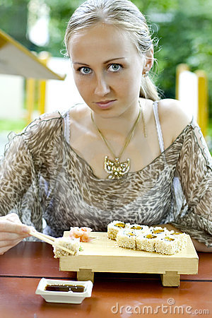 Beautiful woman eating sushi.