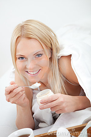 Beautiful woman eating yogurt in bed