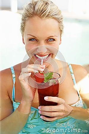 Beautiful woman enjoying a drink in the pool