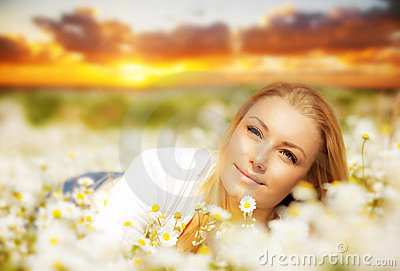 Beautiful woman enjoying flower field on sunset