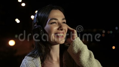 Beautiful woman enjoying music in night city stock video footage