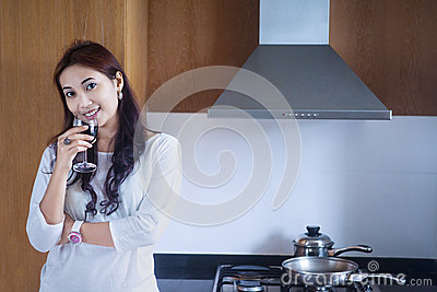 Beautiful woman enjoying wine in kitchen