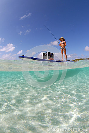 Beautiful woman fishing from paddle board