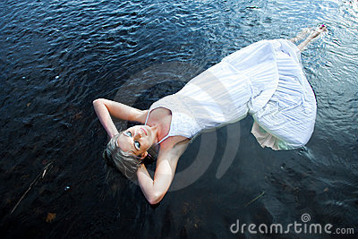 Beautiful woman floating in blue river