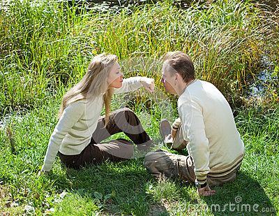 The beautiful woman for fun threatens to knock the man on a nose in the summer on a grass at the lake