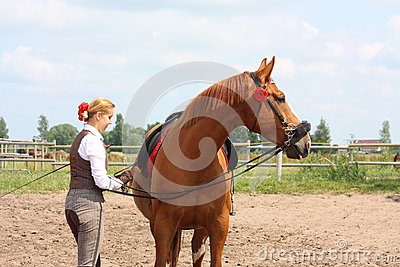 Beautiful woman getting horse ready for the riding