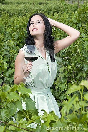 Beautiful woman with glass red wine in vineyard