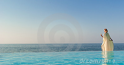 Beautiful woman in greek style on infinity pool