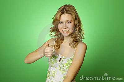 Beautiful woman on green background. Thumbs up