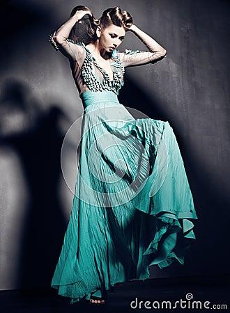 Beautiful woman in green dress posing dramatic indoors