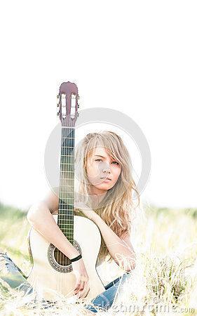 Beautiful woman with guitar sitting on grass.