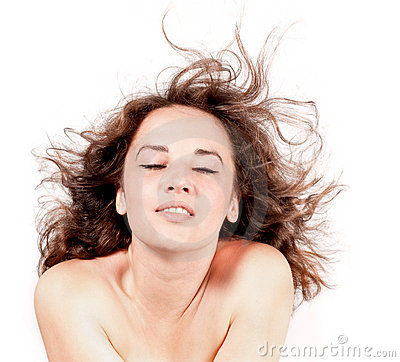 Beautiful woman with hair blown by wind on white