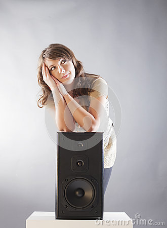 Beautiful woman with hands on big wooden speaker