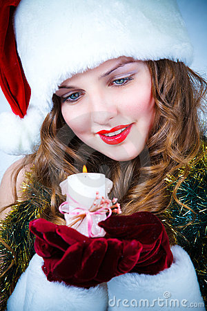 Beautiful woman in hat of Santa with a candle