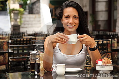 Beautiful woman having coffee in courtyard cafe