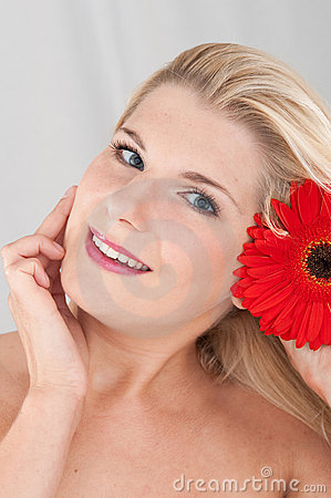 Beautiful woman with a healthy skin and flower