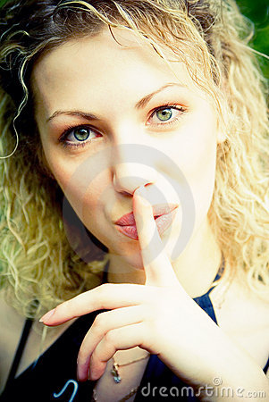 Beautiful woman with her finger over her mou