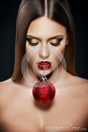 Free Beautiful Woman Holding A Christmas Ornament With Teeth Over Dark Background Stock Image - 79730831