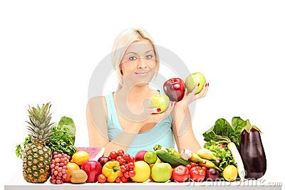 Beautiful woman holding apples behind a table full of fruits
