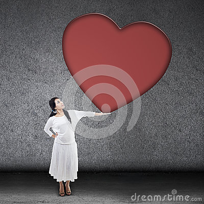 Beautiful woman holding blank heart sign