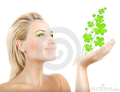 Beautiful woman holding clover leaves