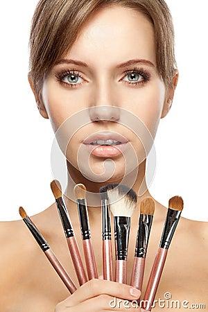 Beautiful woman holding makeup brushes set