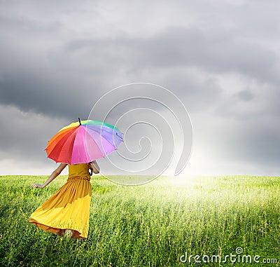 Beautiful woman holding multicolored umbrella in green grass field and raincloud
