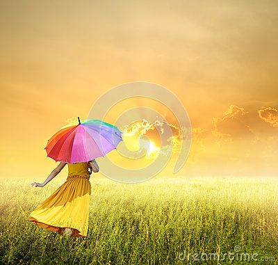 Beautiful woman holding multicolored umbrella in green grass field and sunset
