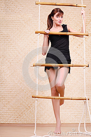 Beautiful woman holds on bamboo rope ladder