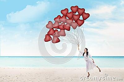 Beautiful woman holds heart balloons