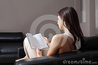Beautiful woman at home sitting on a couch reading a book