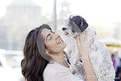 Beautiful woman hugging her little dog outdoor