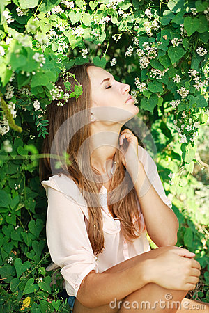 Beautiful woman inhale the aroma of white flowers