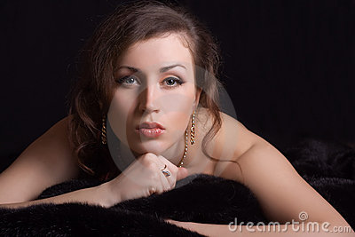 Beautiful woman in jewelry lies on fur