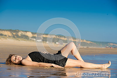 Beautiful woman layed on the snad at the beach