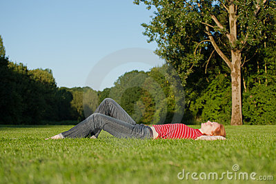 A beautiful woman laying in the park