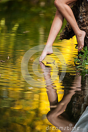 Beautiful woman legs in water in the forest. fairy tale