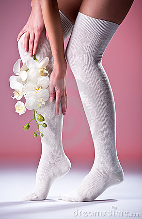 Beautiful woman legs with white orchid