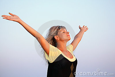 Beautiful woman lifted hands upwards against sky