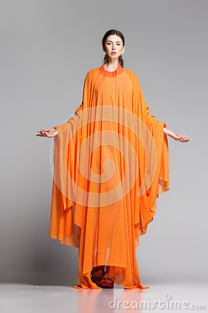 Beautiful woman in long orange dress posing dramatic in the studio